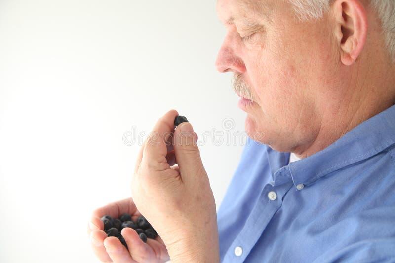 Человек с свежими голубиками стоковые изображения rf