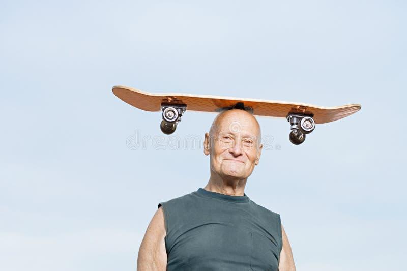 Человек с скейтбордом на его голове стоковые фото
