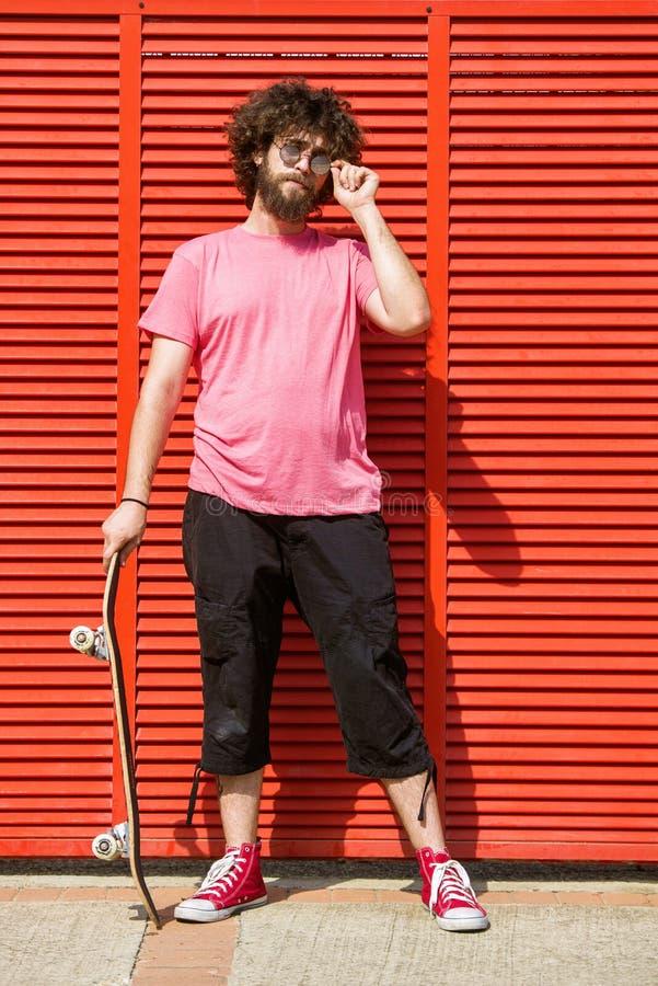 Человек с скейтбордом на красной предпосылке стоковое фото rf
