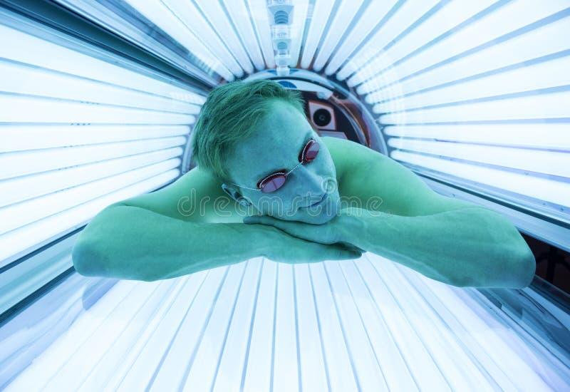 Человек с солнечными очками на загорая кровати в солярии стоковые изображения