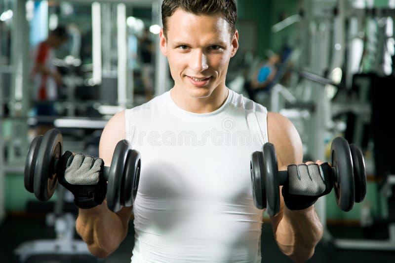 Человек с тренажером веса стоковые фото