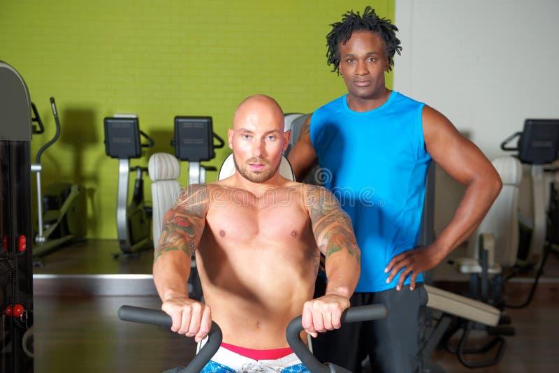 Человек с тренером в спортзале стоковое фото