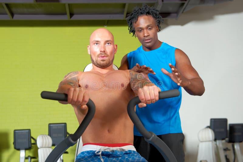 Человек с тренером в спортзале стоковое фото rf