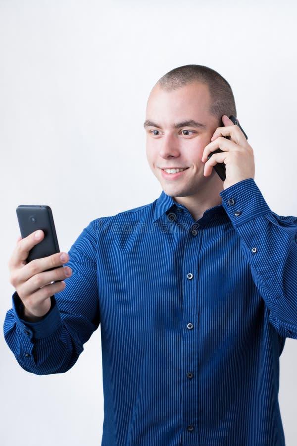 Человек с 2 умными телефонами стоковое фото