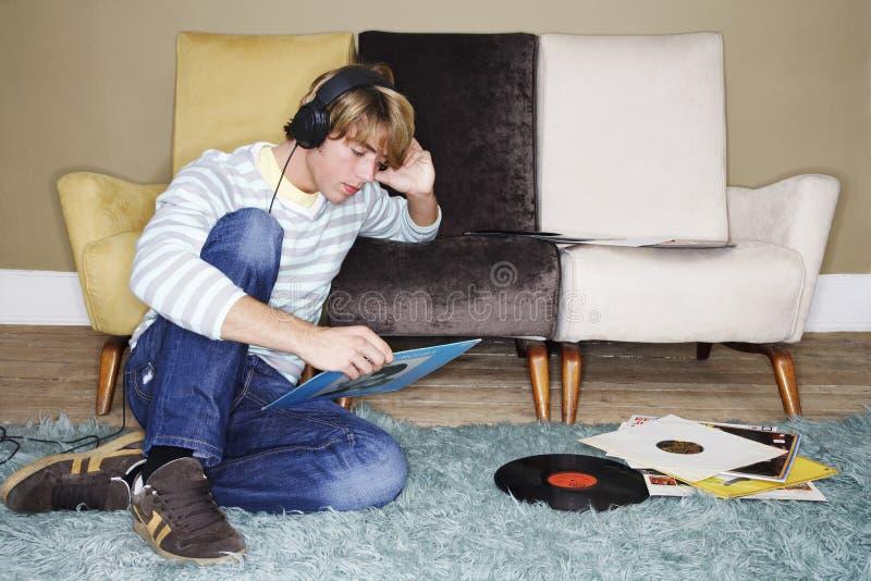 Человек слушая к показателям в живущей комнате стоковая фотография