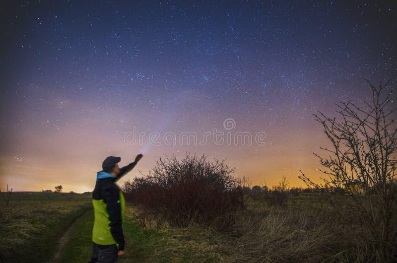 Человек с электрофонарем наблюдающ ночным небом стоковые изображения rf
