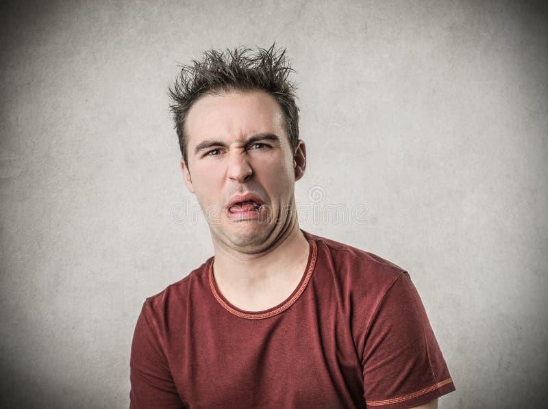 Человек с disgusted выражением стоковые изображения