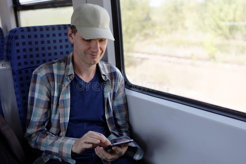 Человек с smartphone в поезде стоковое фото