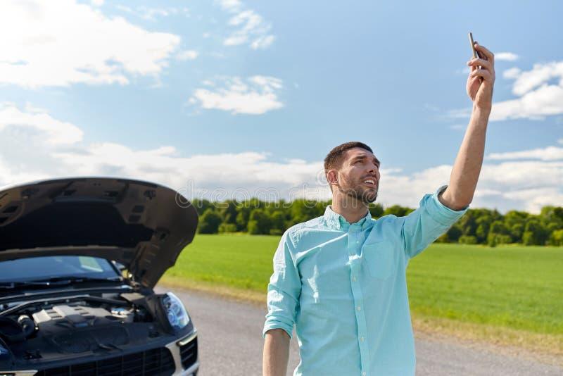 Человек с smartphone и сломленным автомобилем на сельской местности стоковое фото