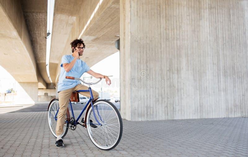 Человек с smartphone и фиксированная шестерня велосипед на улице стоковое фото