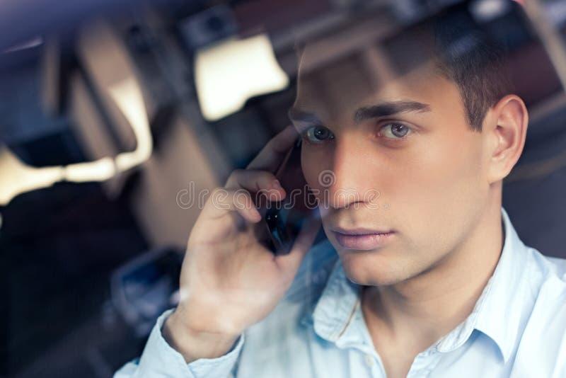 Человек телефонируя в его автомобиле стоковое фото rf
