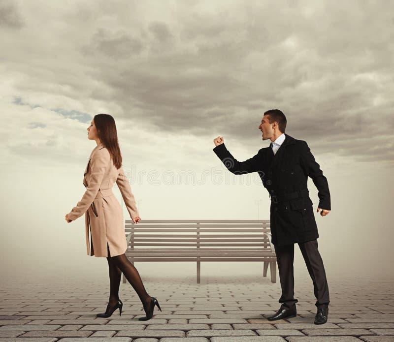 Человек тряся кулак на общительной женщине стоковая фотография rf