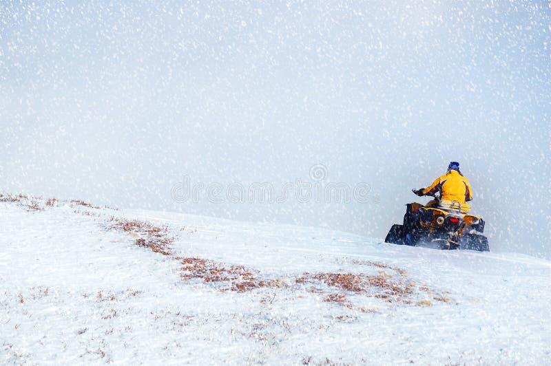 Человек управляя снегоходом в горе зимы Красивые снежности стоковые фотографии rf