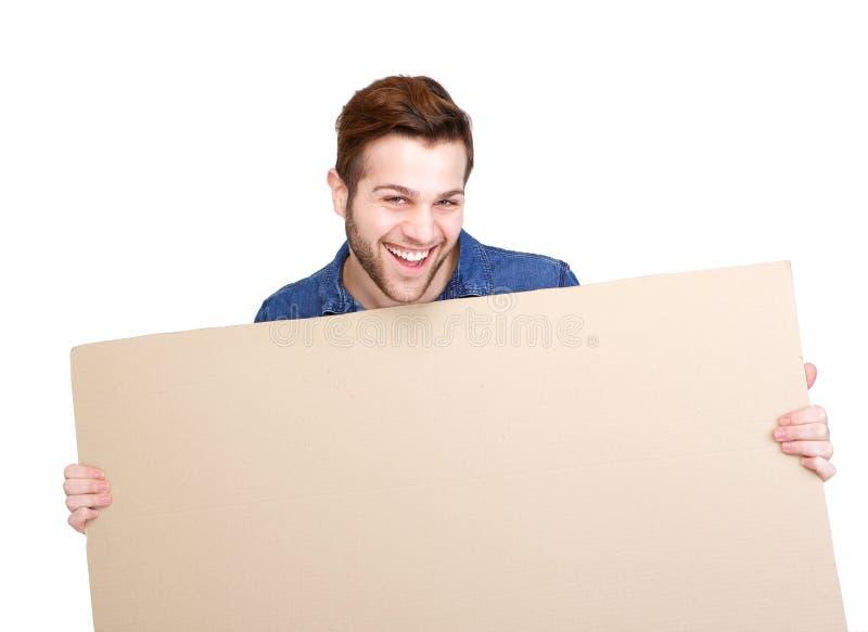 Человек усмехаясь и держа пустой знак стоковая фотография rf