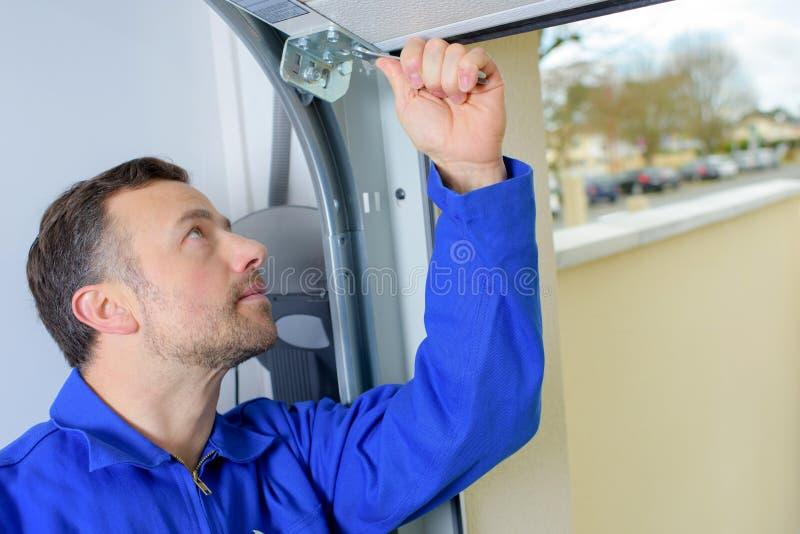 Человек устанавливая дверь гаража стоковое фото rf
