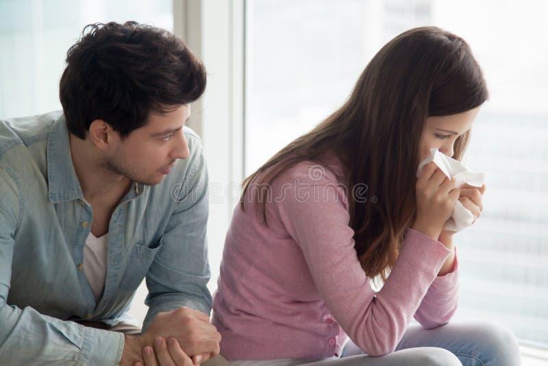 Человек утешая расстроенную женщину плача, парня утешая плача молодой l стоковая фотография