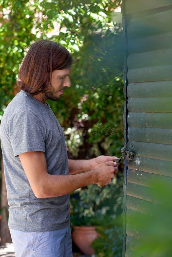 Человек фиксирует дверь мастерской стоковые изображения rf