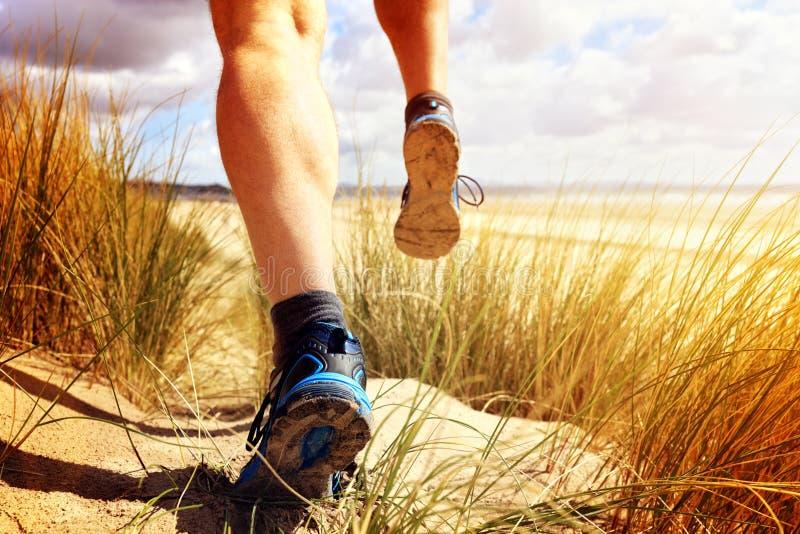 Человек фитнеса бежать на пляже стоковые фото