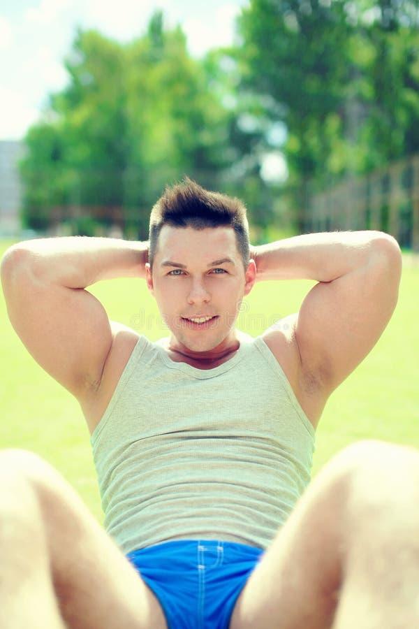 Человек фитнеса делая подбрюшные тренировки грея перед тренировать outdoors, спортсмен портрета на траве стоковое фото