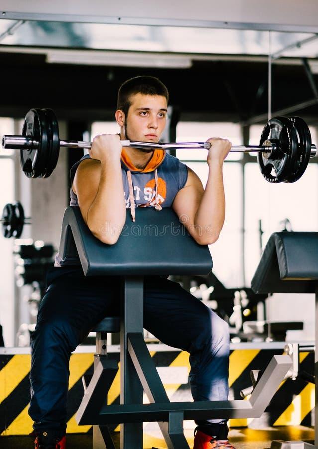 Человек фитнеса работая с штангой в спортзале Подъем человека фитнеса мертвый Спорт и фитнес - концепция здорового образа жизни стоковая фотография rf