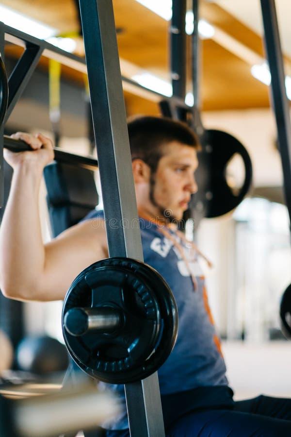Человек фитнеса работая с штангой в спортзале Подъем человека фитнеса мертвый Спорт и фитнес - концепция здорового образа жизни стоковое изображение