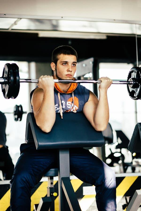 Человек фитнеса работая с штангой в спортзале Подъем человека фитнеса мертвый Спорт и фитнес - концепция здорового образа жизни стоковое изображение rf