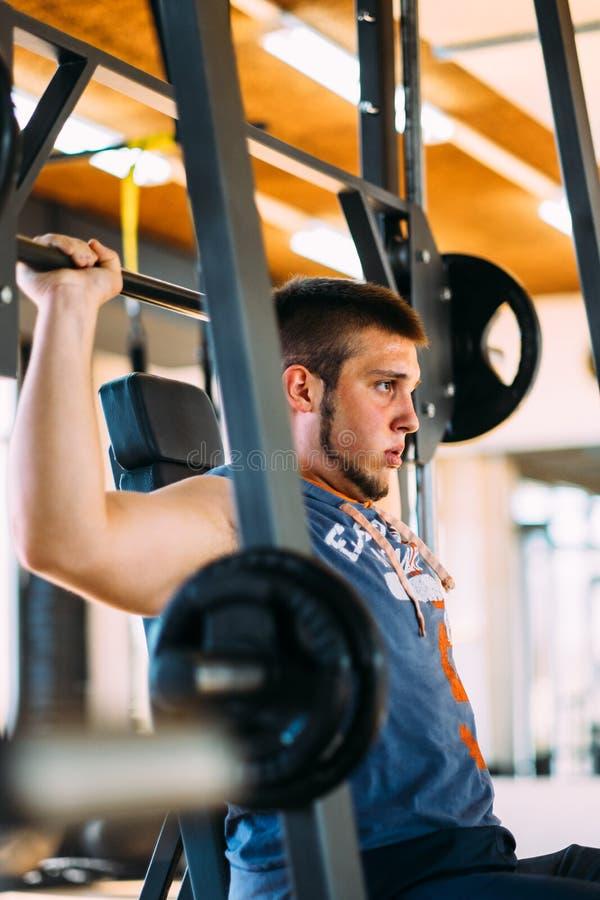 Человек фитнеса работая с штангой в спортзале Подъем человека фитнеса мертвый Спорт и фитнес - концепция здорового образа жизни стоковое фото rf