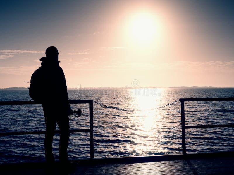 Человек, фотограф принимая фото на озеро на заходе солнца Фотограф хобби на каникулах стоковое изображение