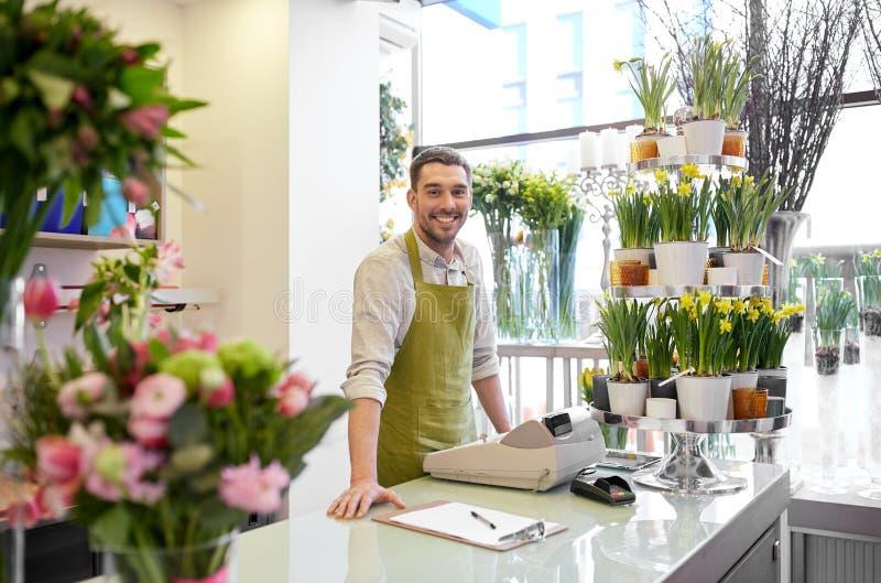 Человек флориста с доской сзажимом для бумаги на счетчике цветочного магазина стоковые фото
