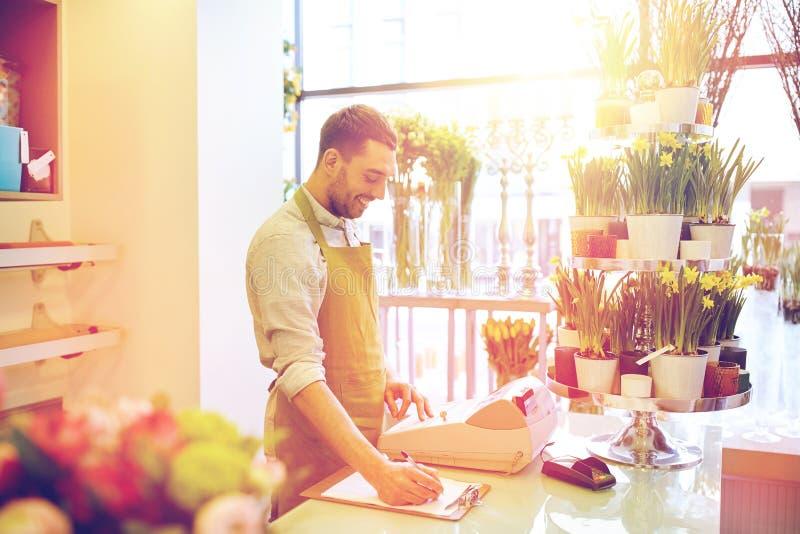 Человек флориста с доской сзажимом для бумаги на счетчике цветочного магазина стоковые фотографии rf