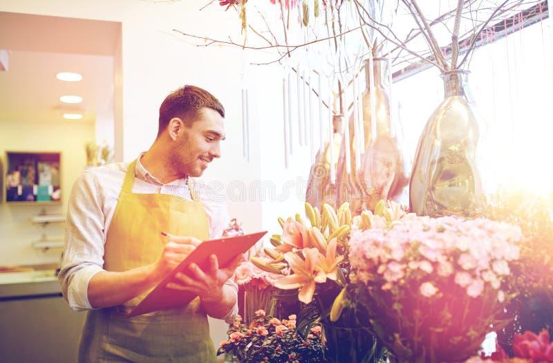 Человек флориста с доской сзажимом для бумаги на цветочном магазине стоковая фотография rf