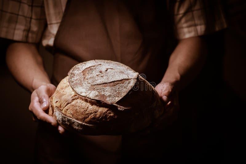 Человек хлебопека держа круглый хлеб стоковые изображения