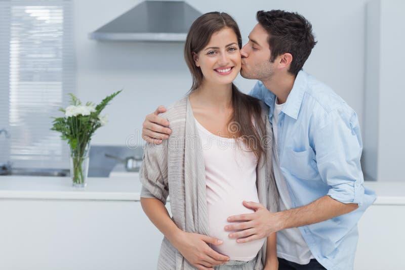 Человек целуя его беременную жену стоковые фотографии rf