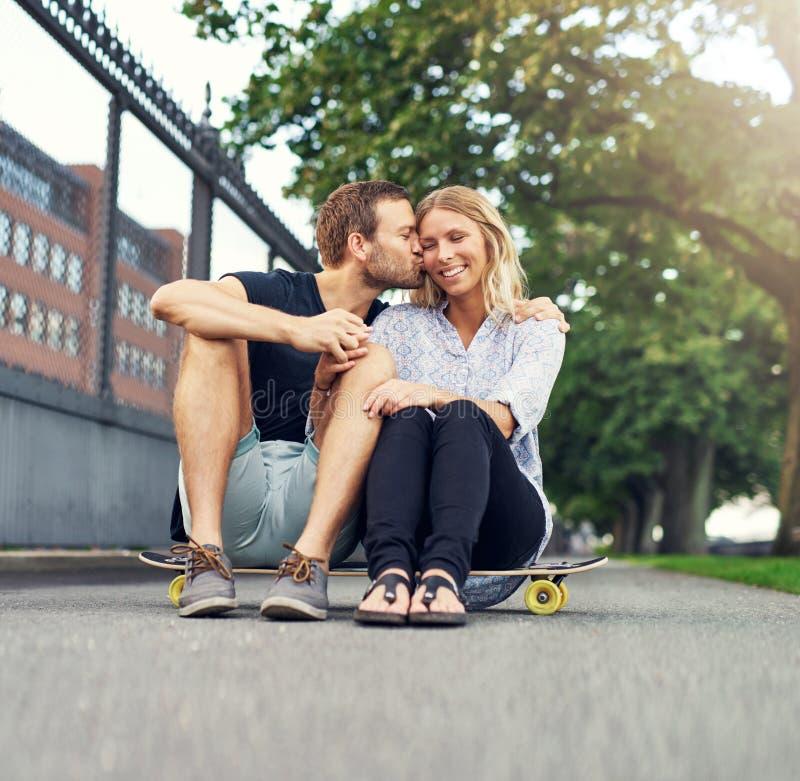 Человек целуя женщину на ее щеке стоковая фотография