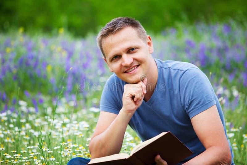 Download Человек читает книгу в поле Стоковое Фото - изображение насчитывающей дело, счастье: 41653236