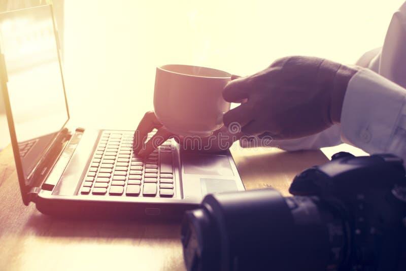 Человек читает новости на компьтер-книжке и выпивая горячем кофе стоковое изображение