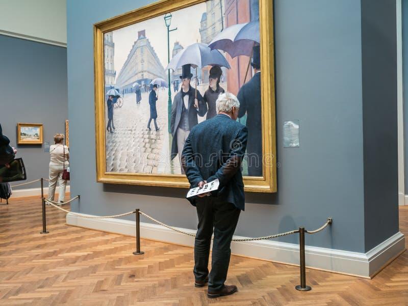 Человек читает ярлык для улицы Парижа Caillebotte, искусство i выставки стоковая фотография rf
