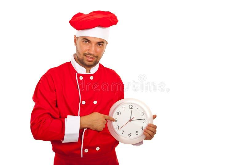 Человек шеф-повара показывает к часам стоковая фотография rf