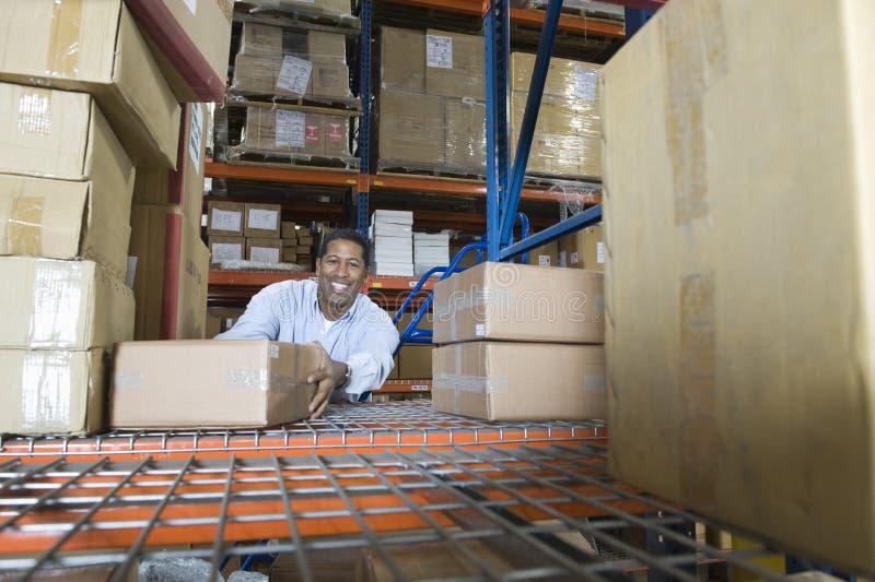 Человек штабелируя коробки в складе стоковое фото rf