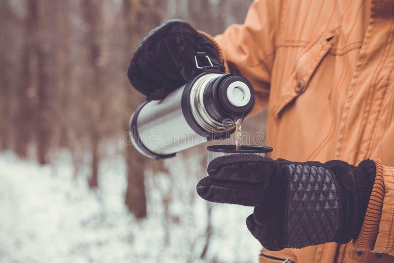 Человек льет чай из thermos стоковые изображения rf