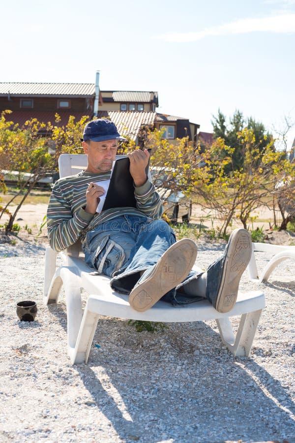 Человек Concentrained сидит на deckchair морем стоковое изображение rf