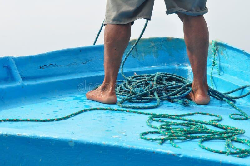 Человек Fisher держа веревочку в шлюпке fisher стоковая фотография