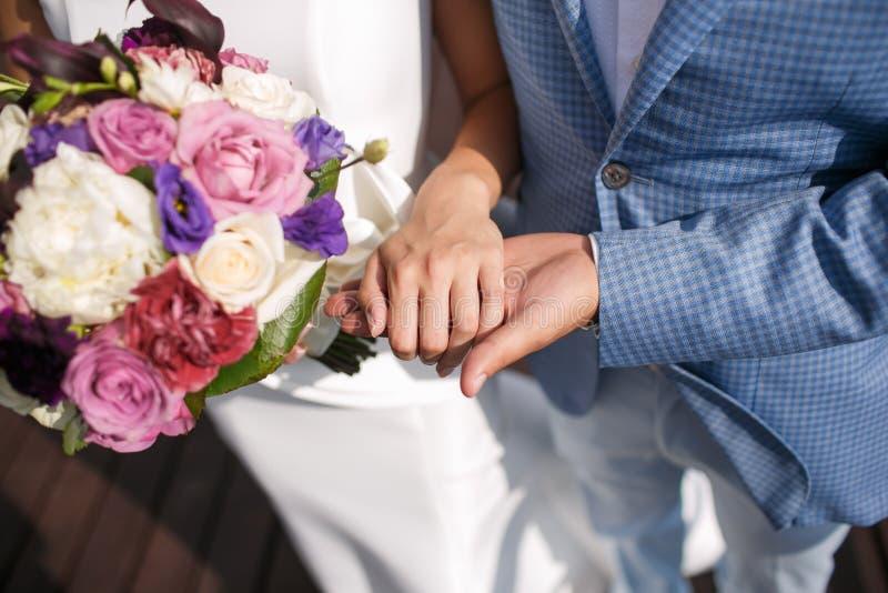 Человек groom держит руку ` s девушки цветастое букета bridal день свадьбы, аксессуары невесты стоковые фото