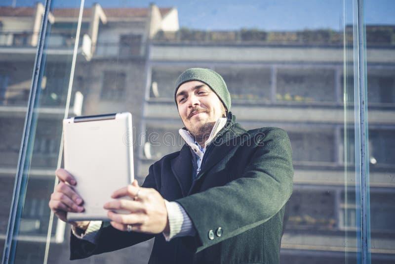 Человек Multitasking используя таблетку, компьтер-книжку и cellhpone стоковая фотография rf