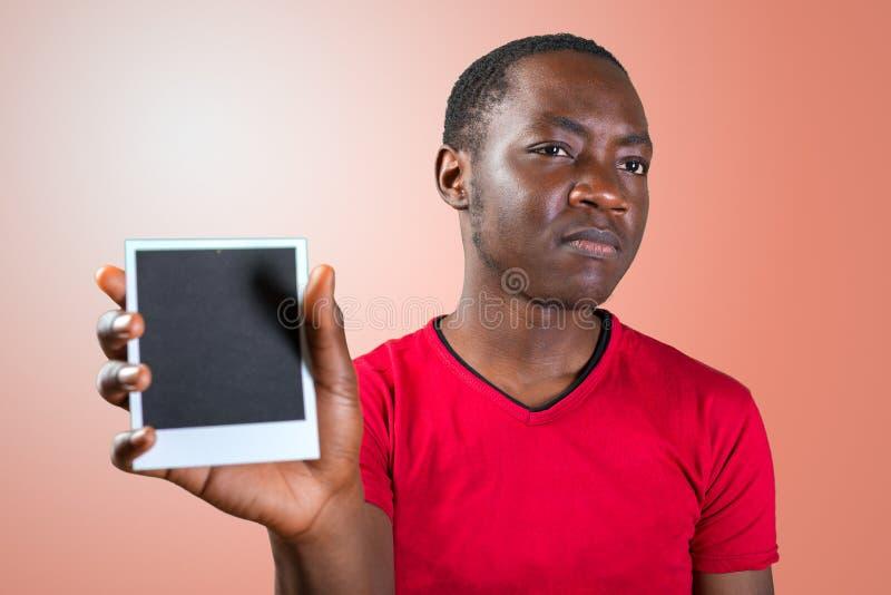 Человек Oung африканский держа пустую черную картинную рамку с космосом экземпляра стоковое изображение