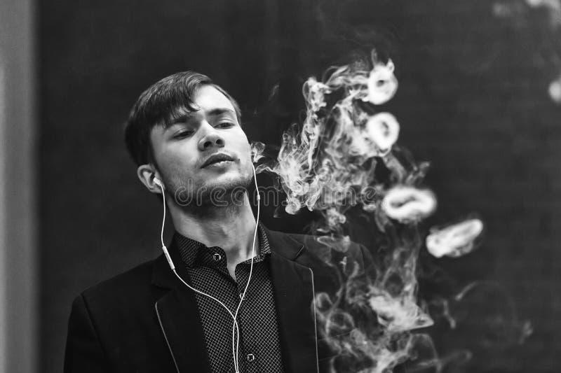Человек Vape Молодой красивый белый парень позволил кольцам из пара от электронной сигареты Пекин, фото Китая светотеневое стоковые изображения rf
