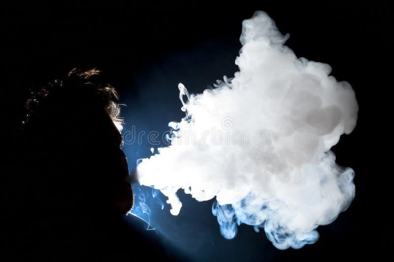 Человек Vaping и дуя облако стоковое фото rf