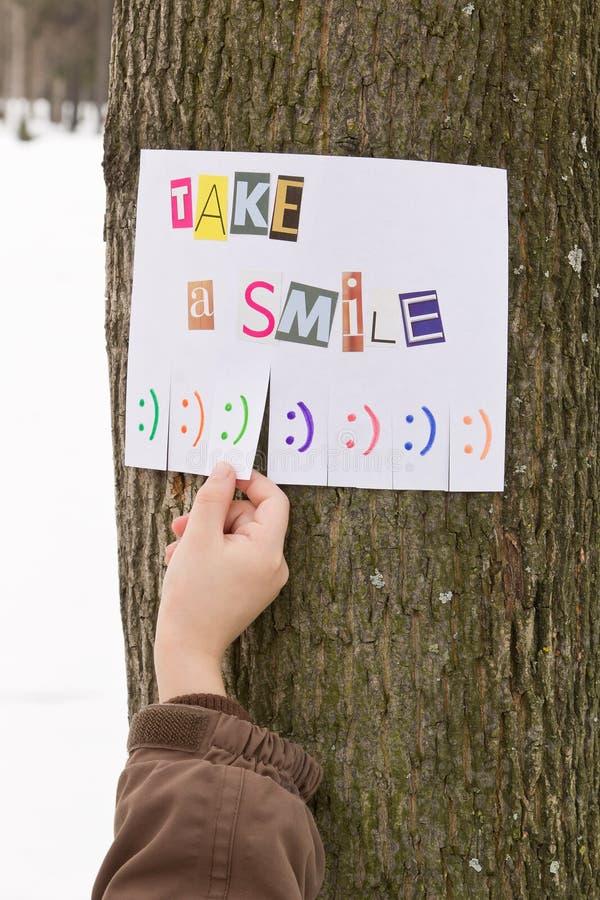 Человеческая рука держит для бумажного объявления с фразой: Примите улыбку и с знаками улыбки готовыми для того чтобы быть оторва стоковые изображения