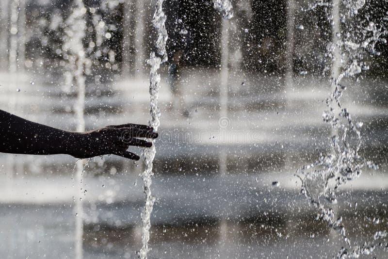 Человеческие рука и фонтан ` s стоковое фото