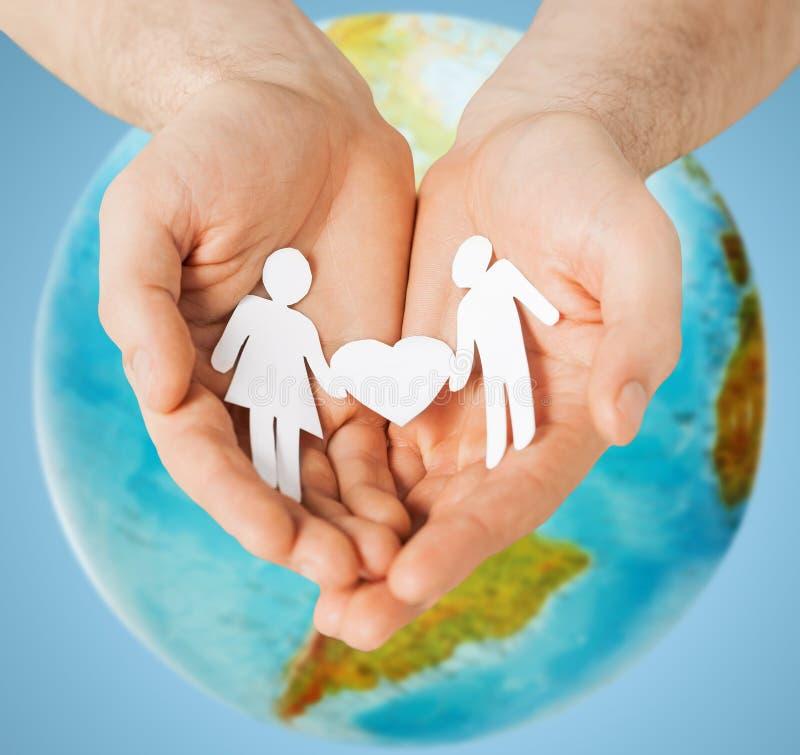 Человеческие руки держа бумажных пар над глобусом земли стоковое изображение